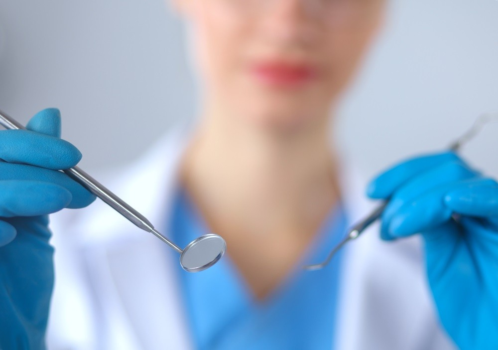 Female dentist holds clean instruments in gloves